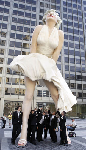 Male members of the Hugh and Anya Nguyen wedding party pose under Seward Johnson&#39;s 26-foot-tall sculpture of Marilyn Monroe, in her most famous wind-blown pose, on Michigan Ave. Friday, July 15, 2011 in Chicago.  <span class=meta>(AP Photo&#47;Charles Rex Arbogast)</span>